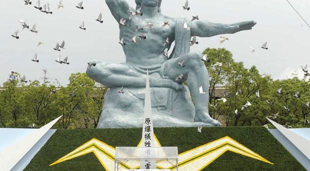Doves fly during a ceremony held in front of the Statue of Peace at Nagasaki Peace Park in Nagasaki, southern Japan (AP)