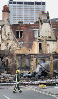 CROYDON, ENGLAND - AUGUST 09: A fire officer walks by the burnt remains of Reeves Corner furniture store on August 9, 2011 in Croydon, England. Emergency services have been cleaning up after a third night of rioting in and around London and other areas of England. (Photo by Peter Macdiarmid/Getty Images)