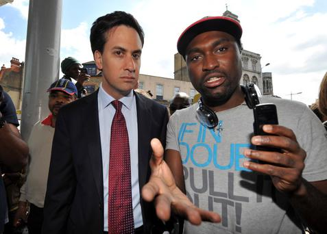 LONDON, UNITED KINGDOM - AUGUST 09: Labour leader Ed Miliband (L) speaks with Stafford Blake from Peckham while visiting the area where rioting took place during the night before on August 9, 2011 in Peckham, south east London, England. Sporadic outbreaks of rioting, looting and clashes with police continued for a third day in separate parts of the capital, which began in Tottenham following the killing of the 29 year-old father of four Mark Duggan by armed police in an attempted arrest on August 4. (Photo by Clive Gee - WPA Pool/Getty Images)