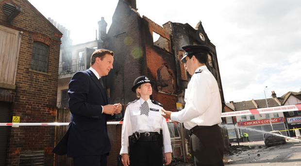 LONDON, UNITED KINGDOM - AUGUST 09: Prime Minister David Cameron talks to Acting Borough Commander Superintendent Jo Oakley (C) during a visit to Croydon to view the destruction from the previous night's violence on August 9, 2011 in London, England. The Prime Minister arrived back from his summer holiday today and in response to the riots recalled parliament to debate the situation on Thursday. (Photo by Stefan Rousseau - WPA Pool/Getty Images)