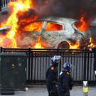 BIRMINGHAM, ENGLAND - AUGUST 09: Police walk past a burning car during riots in Birmingham City Centre on August 8, 2011 in Birmingham, England. After three nights of rioting and looting in and around London, the chaos is starting to spread to other cities around Britain. England. (Photo by Jeff J Mitchell/Getty Images)