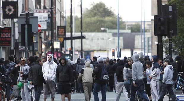 Youths take to the streets in Manchester city centre on a fourth night of rioting in English cities (AP)