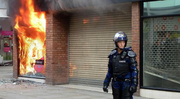 An 18-year-old has been arrested on suspicion of arson after a Miss Selfridge store in Manchester city centre was set alight