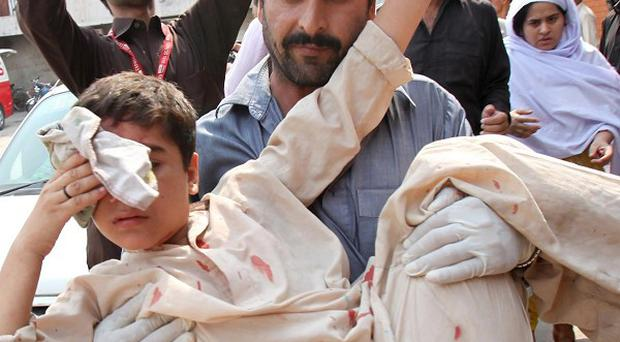 An injured boy is carried to hospital after a bombing in Peshawar (AP)