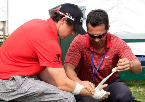 JOHNS CREEK, GA - AUGUST 11: A member of the medical staff examines the right wrist of Rory McIlroy during the first round of the 93rd PGA Championship at the Atlanta Athletic Club on August 11, 2011 in Johns Creek, Georgia. (Photo by Sam Greenwood/Getty Images)