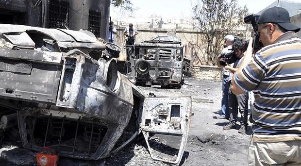 An image released by Syrian official news agency Sana showing burnt police vehicles in Hama (AP)