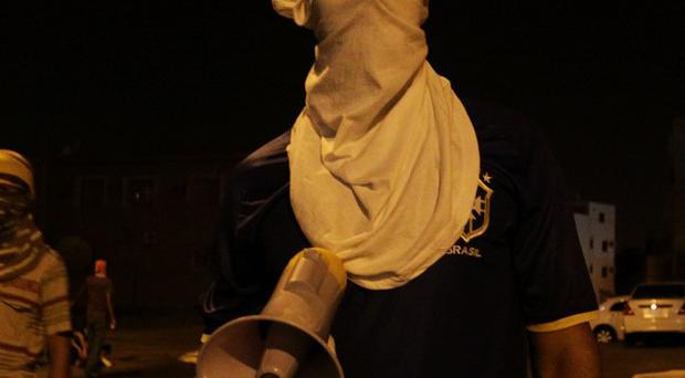 Masked Bahraini youths protest against the government (AP)