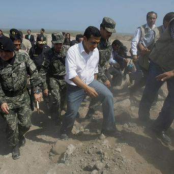 Peru's president Ollanta Humala, centre, walks with army officers during his visit to Pisco, Peru (AP)
