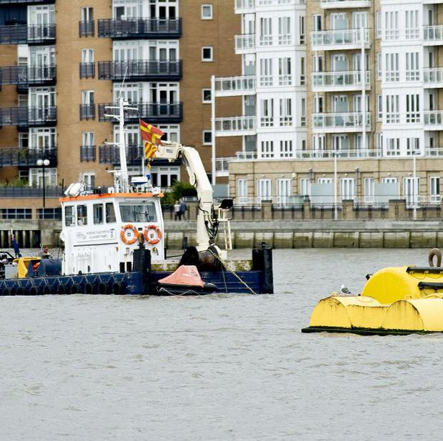 A crane and life raft sit above a tug which sank on the River Thames