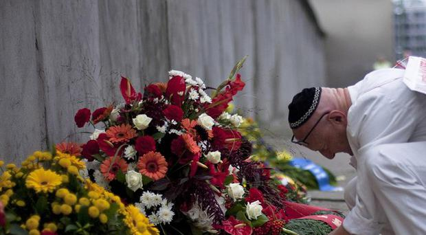 A man lights a candle at the Berlin Wall Memorial at Bernauer Strasse in Berlin (AP)