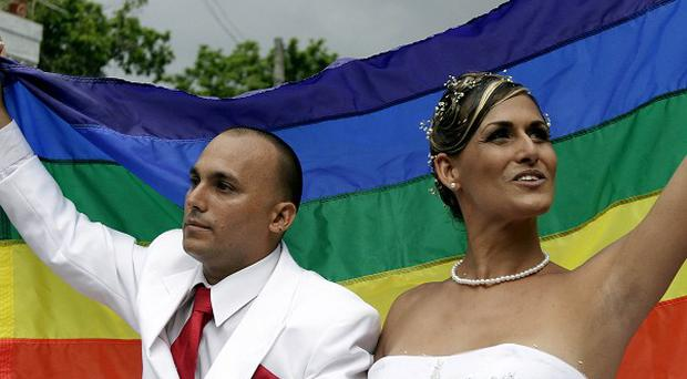 Just married transsexual Wendy Iriepa and Ignacio Estrada hold up a gay rights banner in Havana, Cuba (AP)