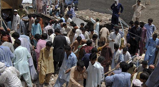 People search for victims through the rubble of a collapsed hotel building after a bomb blast in Dera Allah Yar, Pakistan (AP)
