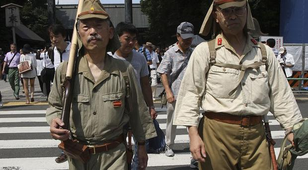 Men in Japanese Imperial Army uniform parade at the Yasukuni Shrine in Tokyo (AP)