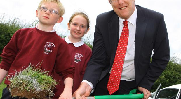 Education Minister John O'Dowd cuts the first sod at St Columba's, with pupils Katie McAuley and Ronan Hamill