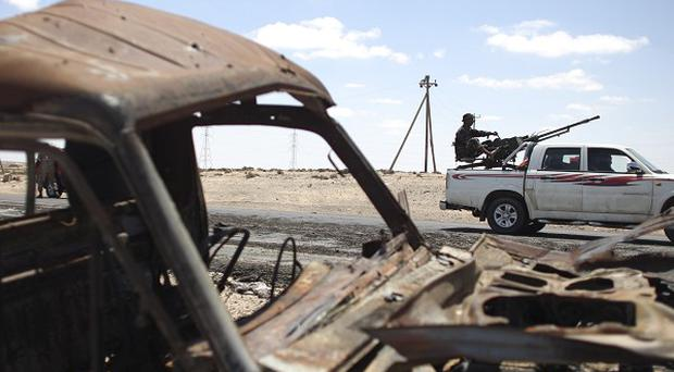 Rebel fighters pass by a destroyed vehicle near the entrance of the town of Brega (AP)