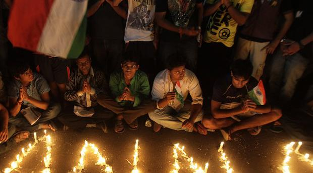 Supporters of Indian anti-corruption activist Anna Hazare gather around lighted candles outside Tihar prison in New Delhi (AP)