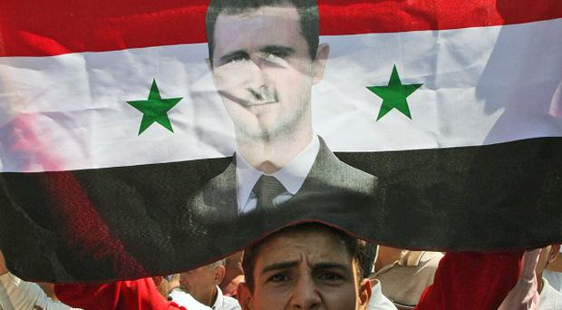 In this photo taken on a government-organised tour, a Syrian man shouts in support of President Bashar Assad in Deir el-Zour (AP)