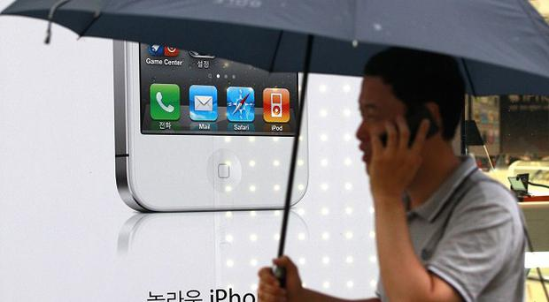 A man passes by an Apple iPhone advertisement in Seoul, South Korea, where more than 25,000 people are suing the company over privacy concerns (AP)