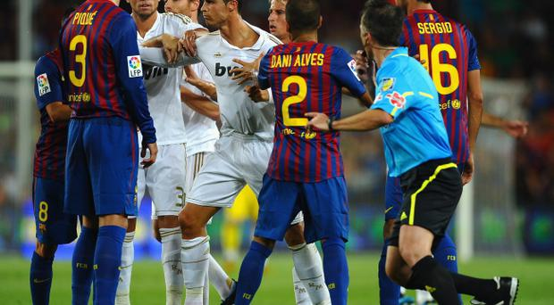 BARCELONA, SPAIN - AUGUST 17: Cristiano Ronaldo of Real Madrid squares up to Andres Iniesta of Barcelona during the second goal during the Super Cup second leg match between Barcelona and Real Madrid at Nou Camp on August 17, 2011 in Barcelona, Spain. (Photo by Laurence Griffiths/Getty Images)