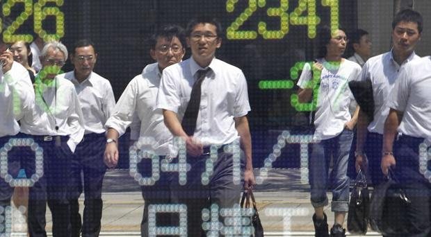 People crossing a street are reflected on the electronic stock board of a securities firm in Tokyo after figures showed Japan's exports fell again (AP)