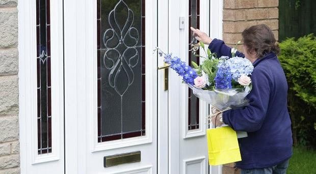 A well-wisher delivers flowers to the Lancashire home of Ian Redmond, who was killed by a shark in the Seychelles on his honeymoon