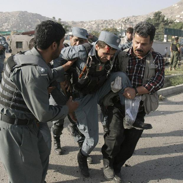 Afghan security forces carry a wounded policeman at the site of a suicide attack outside The British Council in Kabul (AP)