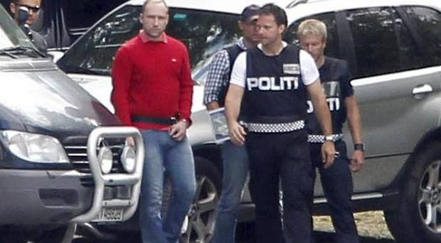 Anders Behring Breivik, in red jumper, is led by police to the quayside to be taken by boat back to Utoya island to explain details of his killing spree (AP)