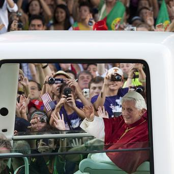 Pope Benedict XVI waves from his Popemobile in Puerta de Alcala square in Madrid (AP)