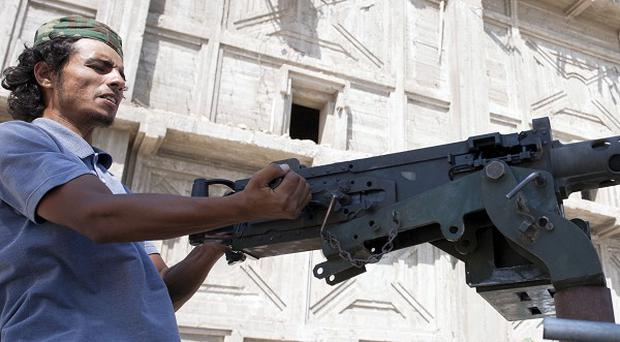 A Libyan rebel fighter readies his weapon before heading to the front line in Tripoli, where loud explosions have been heard (AP)
