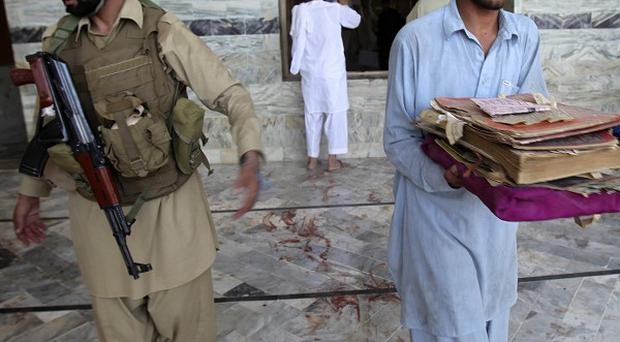 A Pakistani man collects holy books after a suicide bombing at a mosque in Ghundi, in the Pakistani tribal area of Khyber (AP)