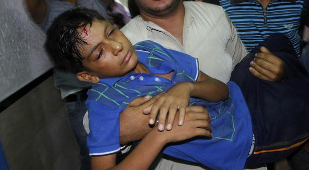 A Palestinian youth, injured during an Israeli airstrike, is carried into Shifa hospital in Gaza City (AP)