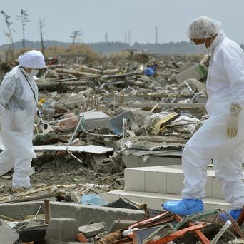 Evacuees wearing radiation protection suits search for their belongings near the Fukushima nuclear plant in Japan (AP)