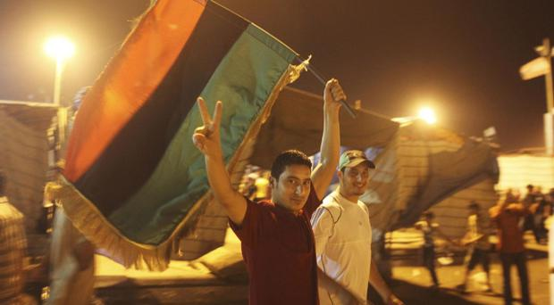 A man flashes the victory sign as he celebrates the capture in Tripoli of Moammar Gadhafi's son and one-time heir apparent, Seif al-Islam, at the rebel-held town of Benghazi, Libya, early Monday, Aug. 22, 2011. Libyan rebels raced into Tripoli in a lightning advance Sunday that met little resistance as Moammar Gadhafi's defenders melted away and his 40-year rule appeared to rapidly crumble. The euphoric fighters celebrated with residents of the capital in the city's main square, the symbolic heart of the regime. (AP Photo/Alexandre Meneghini)