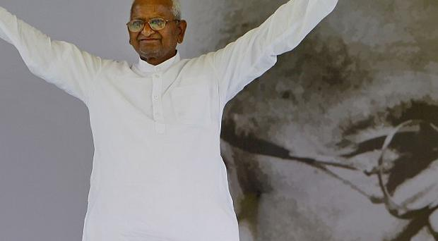Anti-corruption activist Anna Hazare acknowledges his supporters as he stands in front of a portrait of Mahatma Gandhi(AP)
