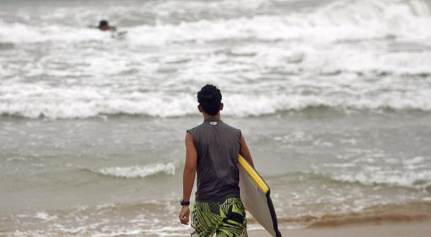 Calm before the storm, a surfer walks into the ocean as tropical storm Irene approaches the island in Luquillo, Puerto Rico(AP)