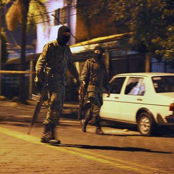 Masked soldiers guard an area in a suburb of Guadalajara, Mexico (AP)