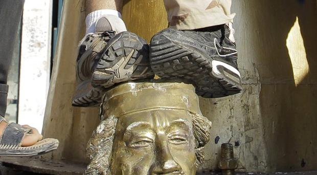 Rebel fighters stand with their feet upon the head of a statue of Muammar Gaddafi after the storming of his Tripoli compound (AP)