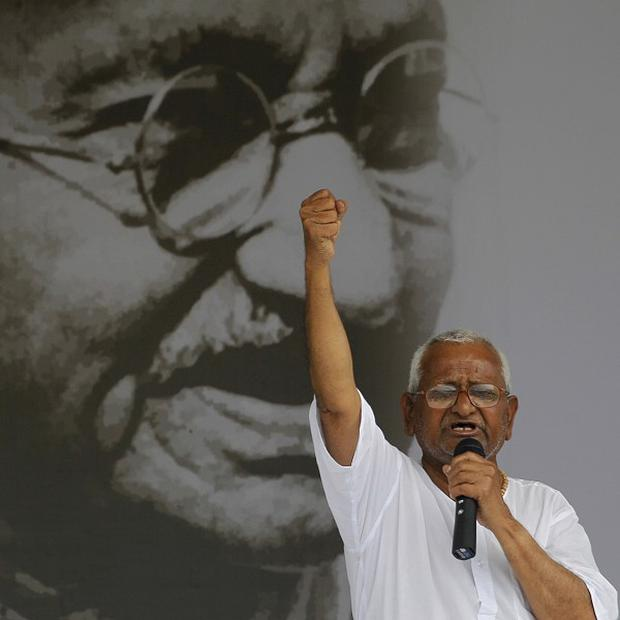India's anti-corruption activist Anna Hazare addresses his supporters in front of a giant portrait of Mahatma Gandhi(AP)