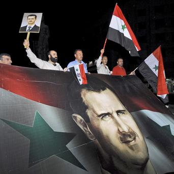 Supporters of President Bashar Assad gather during a protest in Damascus, Syria (AP)