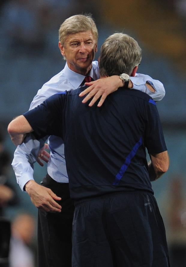 Arsène Wenger embraces his assistant, Pat Rice, after the final whistle last night