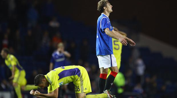 Nikica Jelavic of Rangers and Aleksander Rajcevic of NK Maribor react at the end of the UEFA Europa League play off match between Rangers and Maribor at Ibrox