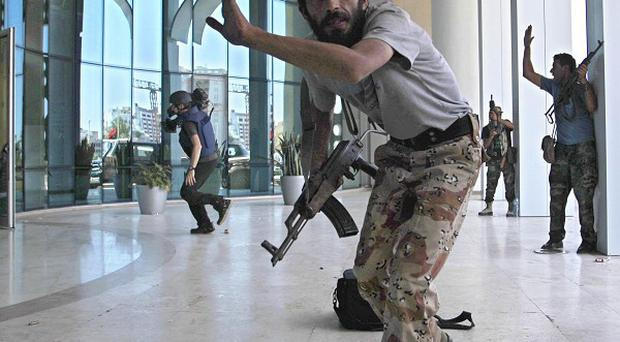 Rebel fighters take shelter as an intense gun battle erupted outside Tripoli's Corinthia hotel, where many foreign journalists are staying (AP)