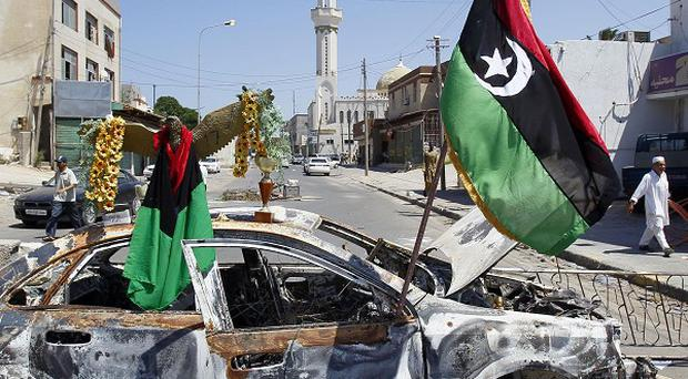 Libya's rebel flag is displayed on a burned car on a check point in Tripoli (AP)