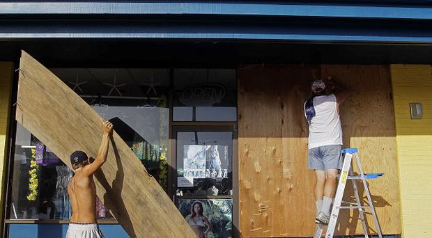 Shop owners place boards over windows in North Carolina in anticipation of Hurricane Irene striking the US coast (AP)