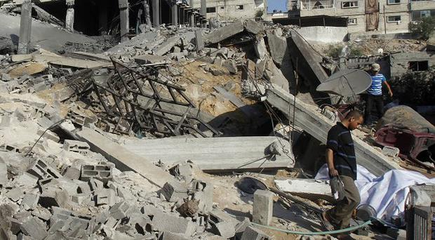 Palestinians inspect a damaged building following an Israeli air strike in the northern Gaza Strip (AP)
