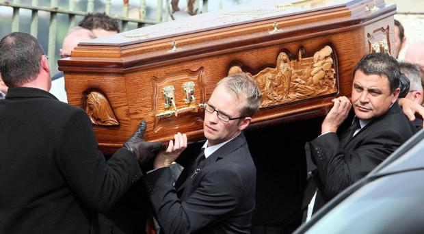 The coffin of Marian Graham is carried by family members into St Mary's church in Newry, Co Down for her funeral