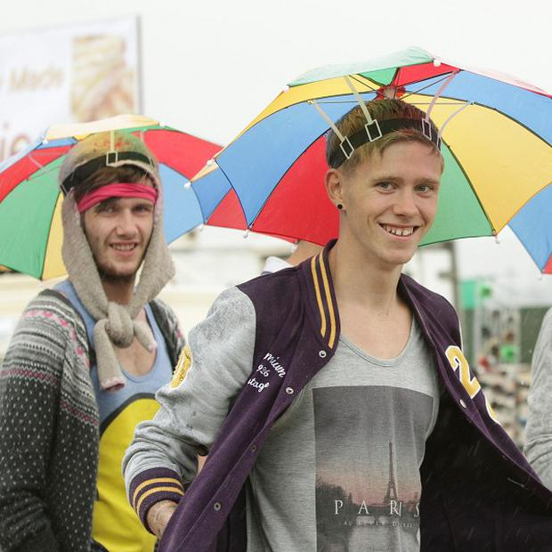 Fans take cover from the rain as they arrive for the Reading Festival