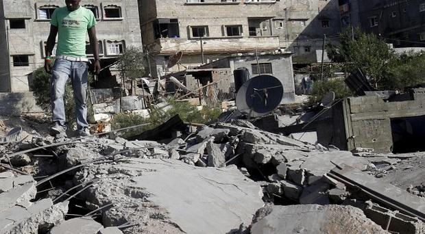 A man inspects the damage caused by an Israeli airstrike in northern Gaza Strip on Thursday, a day before the new ceasefire came into effect