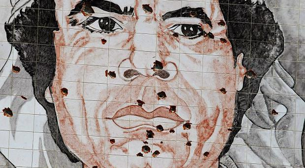 A Gaddafi portrait is seen riddled with bullet holes in Tripoli (AP)