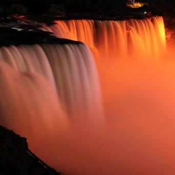 Niagara Falls is illuminated in orange, to honour the late New Democrats party leader Jack Layton (AP)